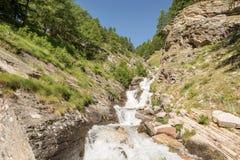 Agua potable de la montaña que fluye abajo de una corriente Foto de archivo libre de regalías