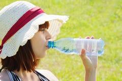 Agua potable de la muchacha al aire libre Imagen de archivo libre de regalías