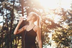 Agua potable de la muchacha atlética en Sunny Park imagen de archivo libre de regalías