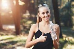 Agua potable de la muchacha atlética feliz fotos de archivo
