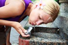 Agua potable de la muchacha atractiva de la fuente Fotos de archivo libres de regalías