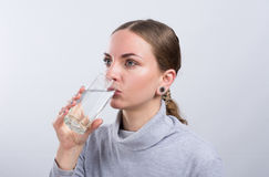 Agua potable de la muchacha atractiva en fondo ligero Imagen de archivo