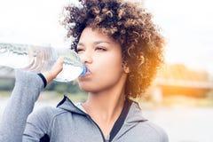 Agua potable de la muchacha de la botella fotos de archivo libres de regalías