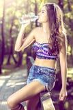 Agua potable de la muchacha de la botella en naturaleza Imagen de archivo