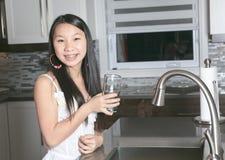 Agua potable de la muchacha del adolescente en la cocina Imagen de archivo libre de regalías