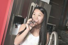 Agua potable de la muchacha del adolescente en la cocina Fotos de archivo libres de regalías