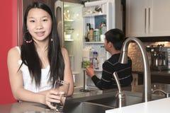 Agua potable de la muchacha del adolescente en la cocina Fotografía de archivo