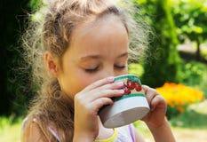 Agua potable de la muchacha del niño de la taza Imagen de archivo libre de regalías