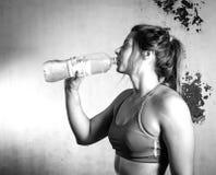 Agua potable de la muchacha después de entrenar Imagen de archivo libre de regalías