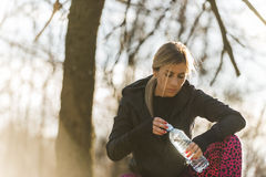Agua potable de la muchacha durante el entrenamiento en la naturaleza Foto de archivo libre de regalías