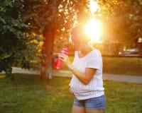 Agua potable de la muchacha embarazada de la botella Fotos de archivo libres de regalías