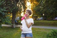 Agua potable de la muchacha embarazada de la botella Imagen de archivo