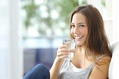 Agua potable de la muchacha en casa Foto de archivo