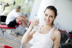 Agua potable de la muchacha en la gimnasia Fotos de archivo