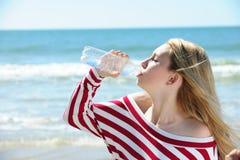 Agua potable de la muchacha en la playa fotografía de archivo libre de regalías