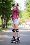 Agua potable de la muchacha en parque con sus cuchillas encendido Fotografía de archivo