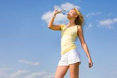 Agua potable de la muchacha hermosa contra el cielo azul foto de archivo libre de regalías