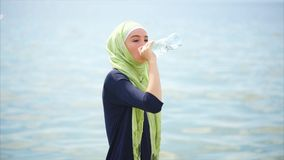 Agua potable de la muchacha musulmán después del entrenamiento al aire libre almacen de metraje de vídeo