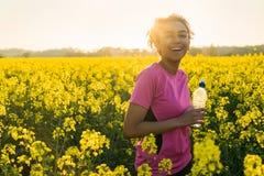 Agua potable de la muchacha de la raza mixta del corredor afroamericano del adolescente Fotografía de archivo libre de regalías