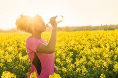 Agua potable de la muchacha de la raza mixta del corredor afroamericano del adolescente Imagenes de archivo