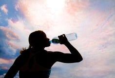 Agua potable de la muchacha rubia joven hermosa Foto de archivo