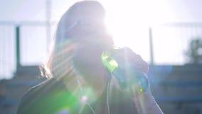 Agua potable de la muchacha de una botella de cristal en la luz del sol hermosa Iluminación muy hermosa C?mara lenta cinem?tica metrajes