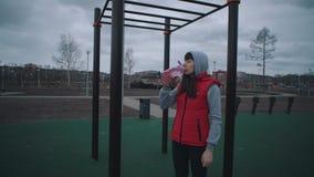Agua potable de la muchacha de una botella reutilizable almacen de video