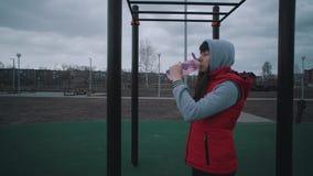 Agua potable de la muchacha de una botella reutilizable metrajes