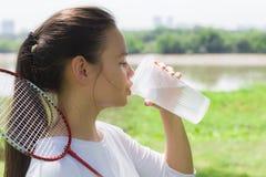 Agua potable de la mujer atlética al aire libre fotografía de archivo