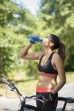 Agua potable de la mujer atlética después del ejercicio con la bicicleta imagen de archivo