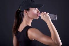 Agua potable de la mujer atractiva apta después del entrenamiento Imagenes de archivo