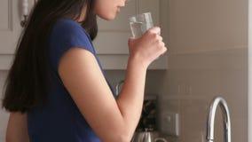 Agua potable de la mujer bastante joven en la cocina almacen de video