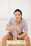 Agua potable de la mujer de la botella en club de salud Imágenes de archivo libres de regalías