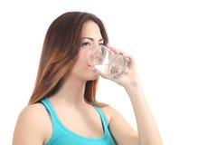 Agua potable de la mujer de un vidrio Imagen de archivo libre de regalías