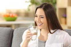 Agua potable de la mujer de un vidrio Foto de archivo libre de regalías