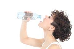 Agua potable de la mujer de una botella plástica Fotos de archivo
