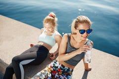 Agua potable de la mujer del corredor en la playa con el funcionamiento asiático del amigo imagen de archivo libre de regalías