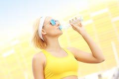 Agua potable de la mujer delante de Amber Stadium Fotografía de archivo