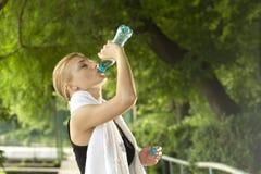 Agua potable de la mujer deportiva Imagen de archivo