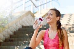Agua potable de la mujer deportiva después de activar fotos de archivo libres de regalías