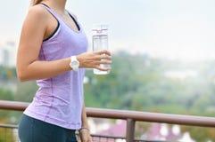 Agua potable de la mujer deportiva después de activar en el parque fotografía de archivo libre de regalías