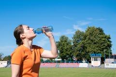 Agua potable de la mujer después de activar foto de archivo libre de regalías