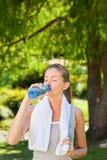 Agua potable de la mujer después de la gimnasia Imágenes de archivo libres de regalías