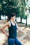 Agua potable de la mujer después del ejercicio en parque Fotografía de archivo libre de regalías