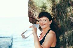 Agua potable de la mujer después del ejercicio en parque Imagen de archivo