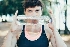 Agua potable de la mujer después del ejercicio en parque Imagen de archivo libre de regalías