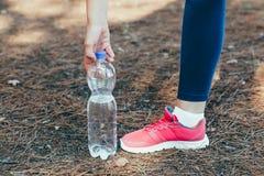 Agua potable de la mujer después del ejercicio en parque Imagenes de archivo