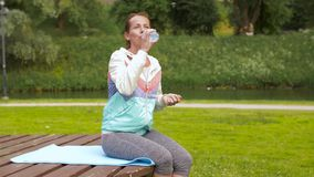 Agua potable de la mujer después de ejercitar en parque metrajes