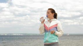 Agua potable de la mujer después de ejercitar en la playa metrajes