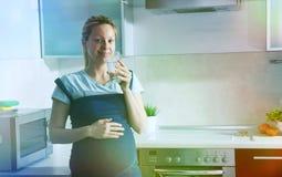 Agua potable de la mujer embarazada Fotografía de archivo libre de regalías
